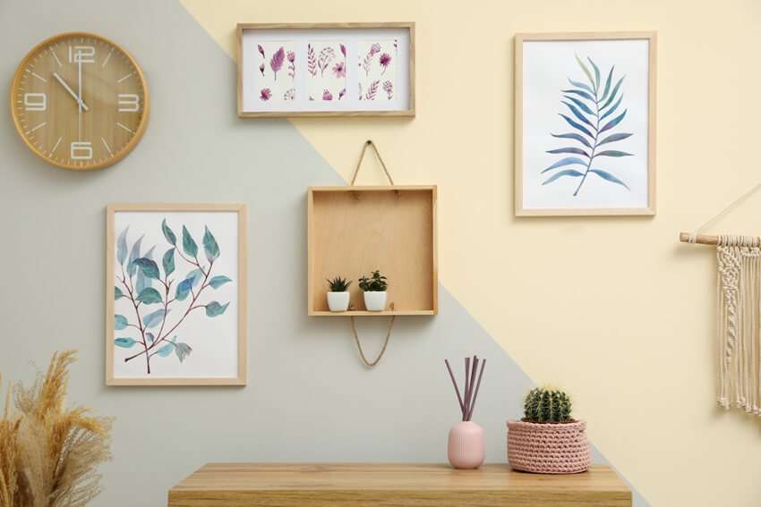 Stylish room interior design with floral paintings and frames hanging on the wall
