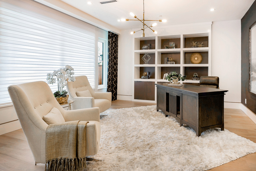 Stylish spacious home office interior with rug light fixture and armchair sofas