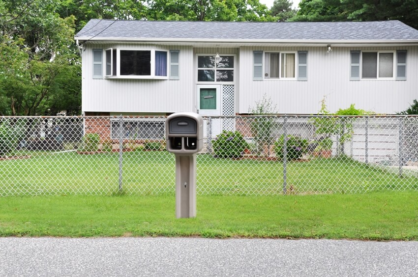 Suburban residential high ranch style home with chain link fence with curbside mailbox