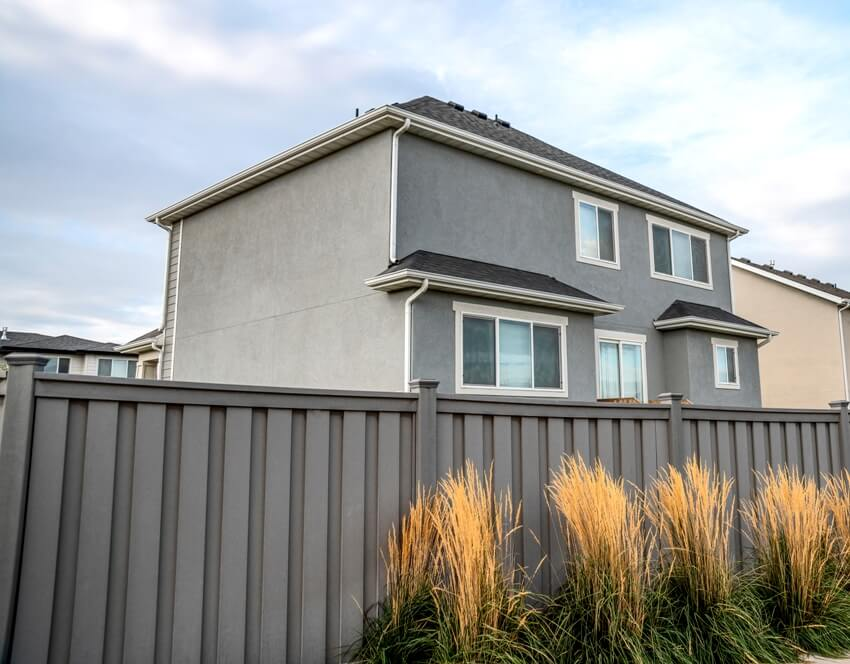 Tall grasses against the gray vinyl fence of a residential area