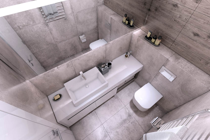 Tiny bathroom with sink mirror toilet and concrete walls and floors