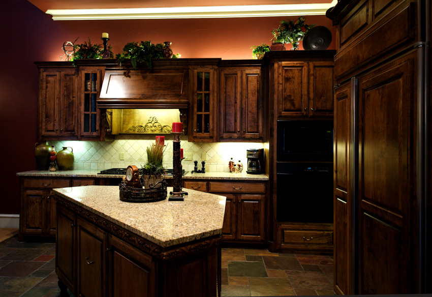 Tuscan kitchen with dark wood theme wooden cabinets center island marble countertop hood