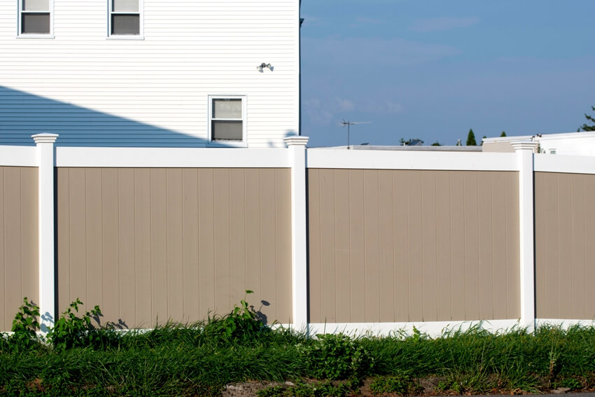 White and beige vinyl fence outside a residential home