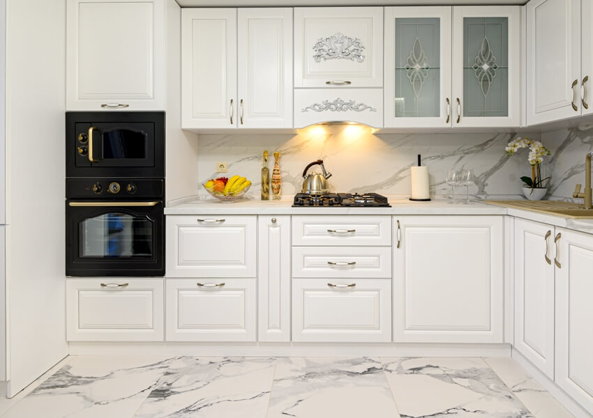 White cozy modern classic kitchen interior with wooden furniture and appliances and marble floor tiles