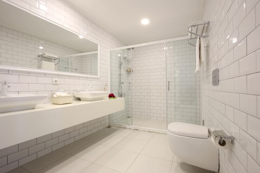 White fully tiled bathroom interior with big mirror