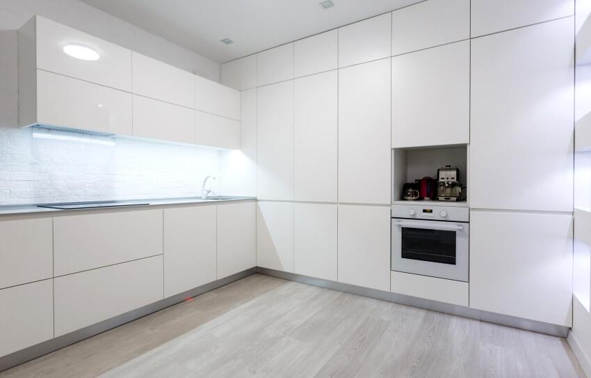 White modern kitchen interior with wooden floors