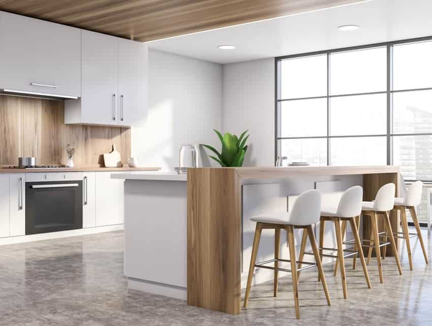 White modern kitchen with island chairs and windows