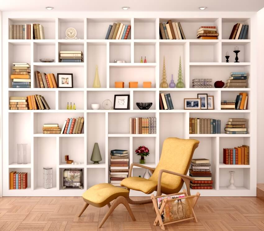White shelves with books and a mustard reclining chair