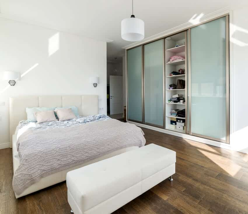 A white sunny bedroom with sliding wardrobe and wooden floors