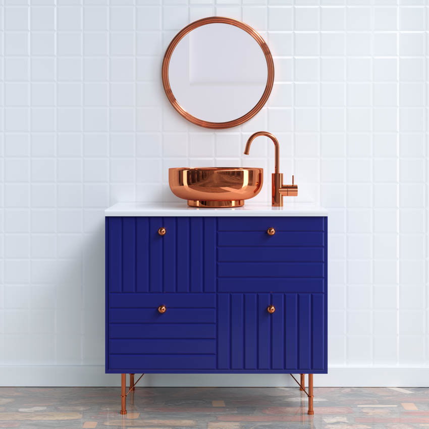White tiled wall blue cabinet copper frame mirror sink and faucet