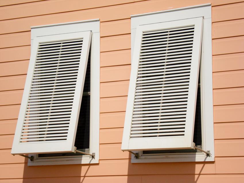 White vertical hurricane shutters on windows orange house siding
