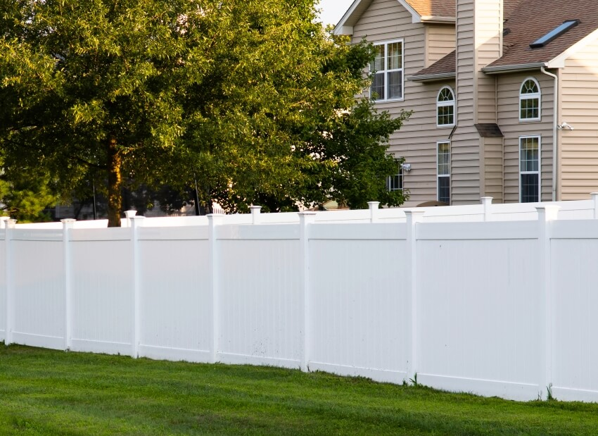 White vinyl fence outdoor backyard home with surrounding trees and green grass