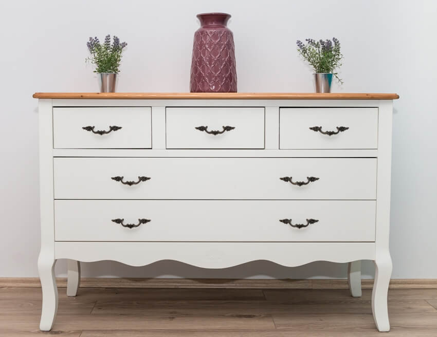 White wooden shabby chic dresser with three vases and flowers on white wall background