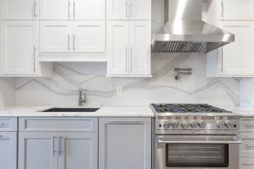 Contemporary kitchen with quartz backsplash and quartz countertops with two tone cabinetry