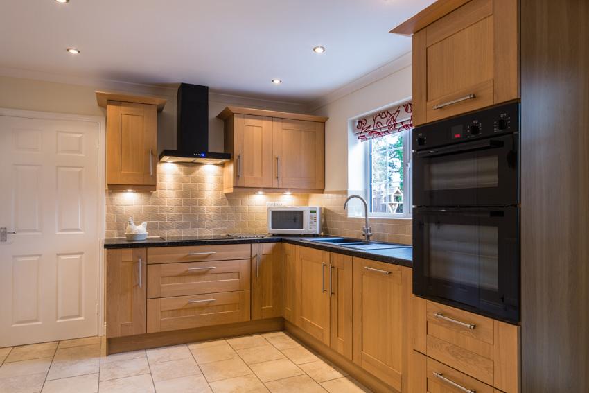 Wood cabinets drawers under cabinet lighting window countertop backsplash