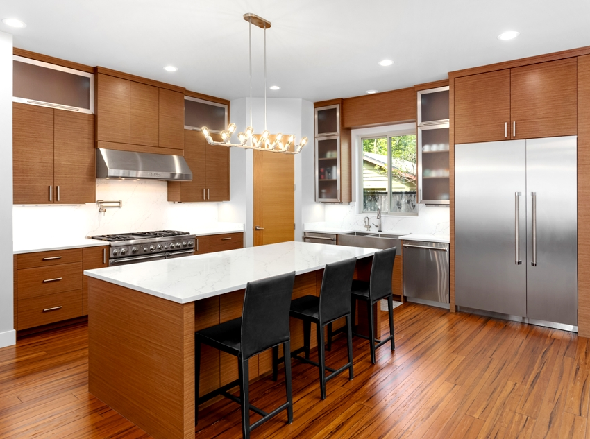 Wooden kitchen interior with stainless steel appliances kitchen island with black chairs and marble countertop