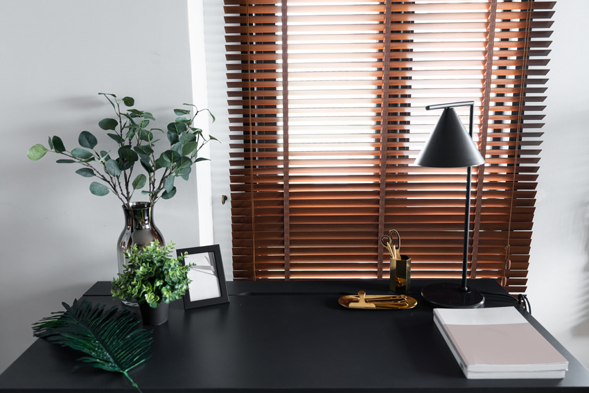 Work corner in home with decorative plant and faux wood blinds
