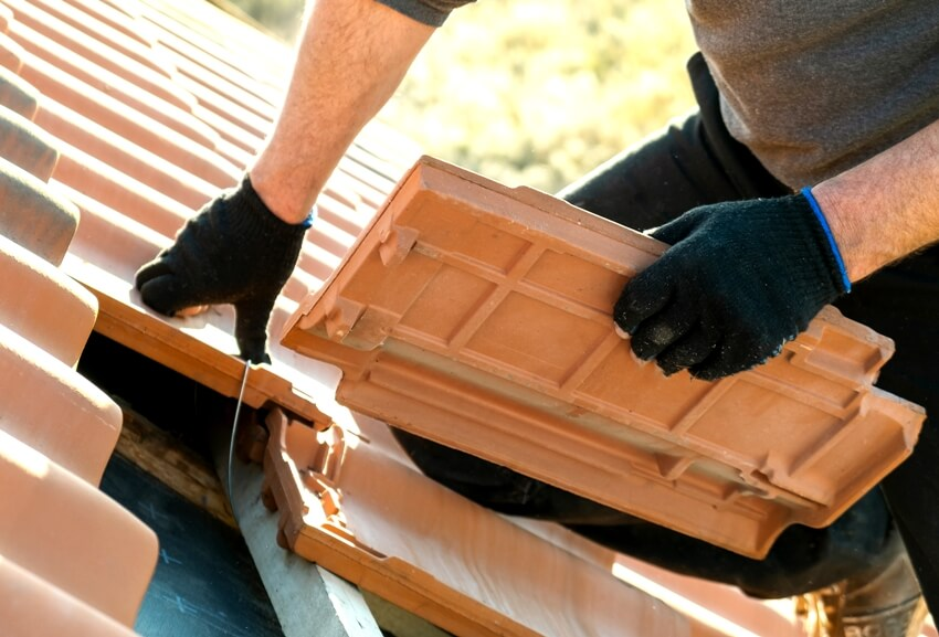 Worker hands installing yellow ceramic roofing tiles mounted on wooden boards covering residential building roof
