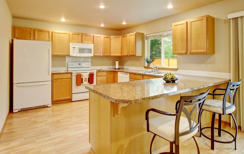 Yellow light tone kitchen with wood cabinets and white appliances