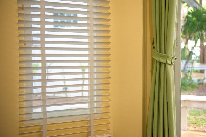Yellow wall window shutter green curtain
