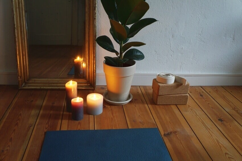 Yoga mat on wooden floor with candles mirror yoga blocks plant in the background