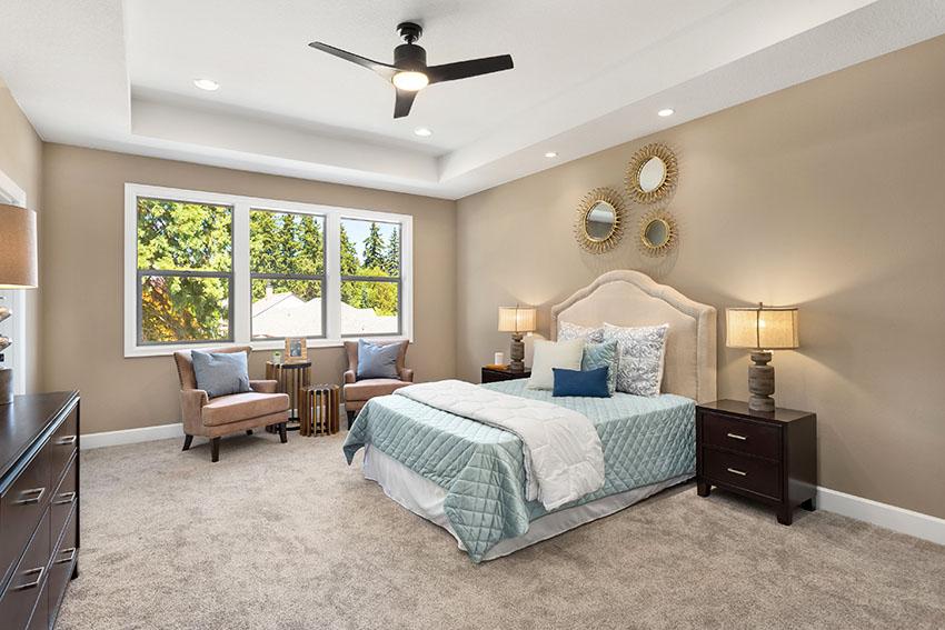 El dormitorio está sombreado con una lámpara de ventilador de techo de pintura marrón oculta en el techo