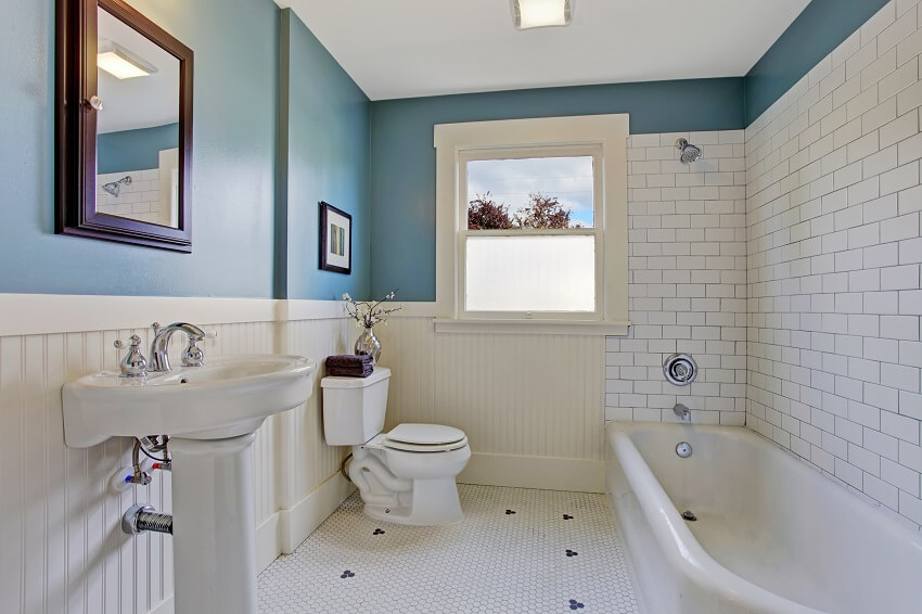 Bathroom interior with beadboard wall, blue wall and white plank panel trim