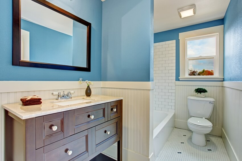 Bathroom interior with blue wall and white plank panel trim bath tub with tile wall trim and brown vanity cabinet with mirror