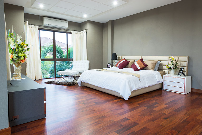 Beautiful bedroom with cherry stained acacia hardwood flooring