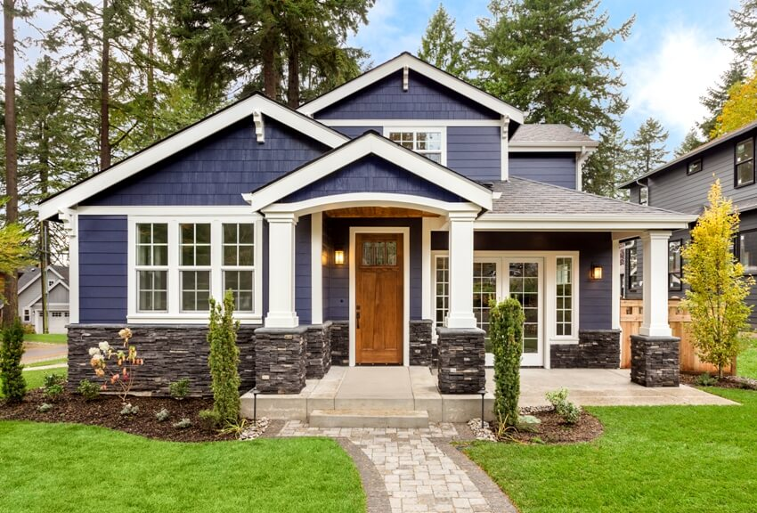 Beautiful exterior of luxury home covered porch and front entrance with green grass yard and walkway