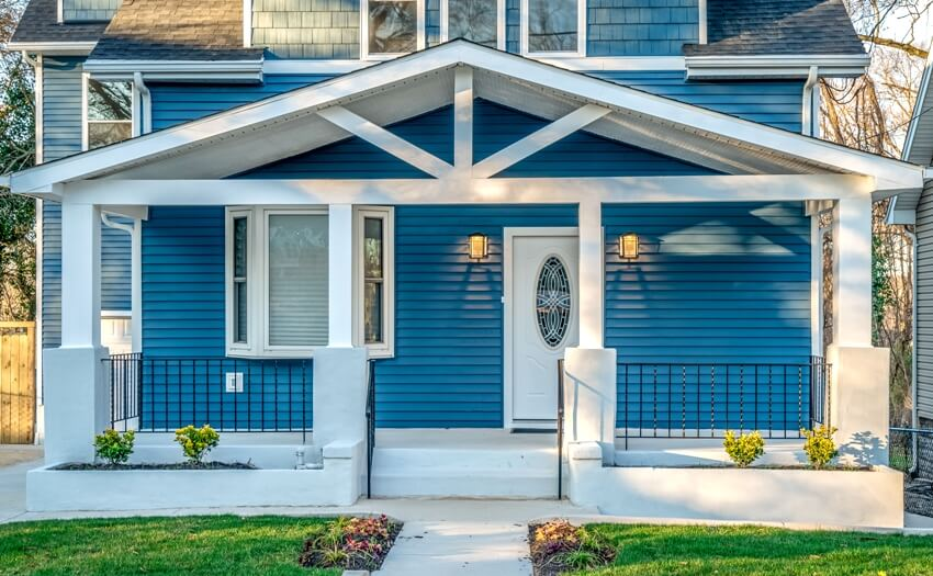A beautiful house with porch white columns beams black baluster railing in front of a blue horizontal vinyl lap siding
