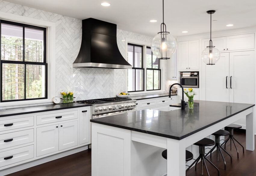 Beautiful kitchen in new luxury home with white cabinets and black accents including black island countertop and backsplash