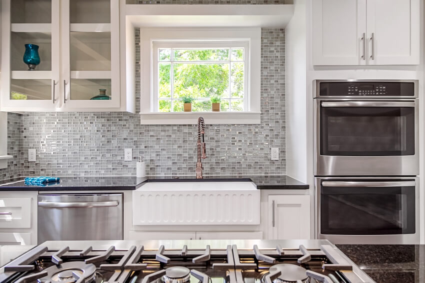 Beautiful kitchen with white cabinets stainless steel appliances black quartz countertops and nice tile backsplash