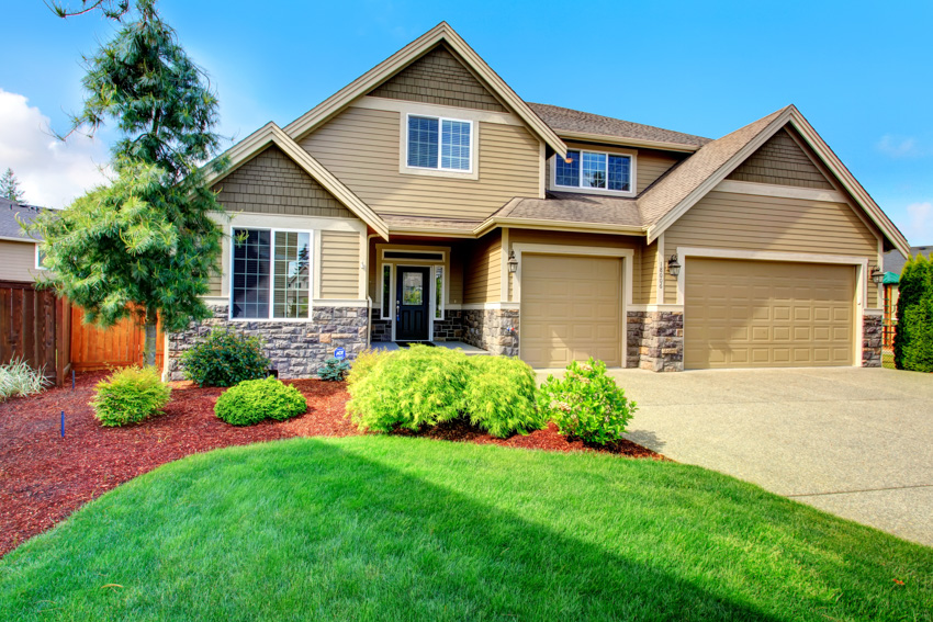 Beige house with clapboard sidings garage driveway landscaped front area