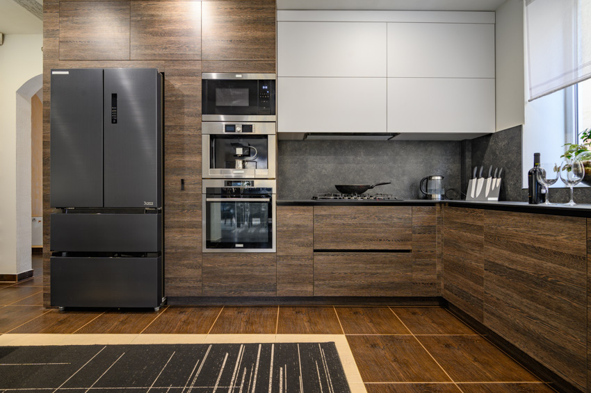 Black stainless steel appliances wood and white kitchen cabinets oven tile flooring