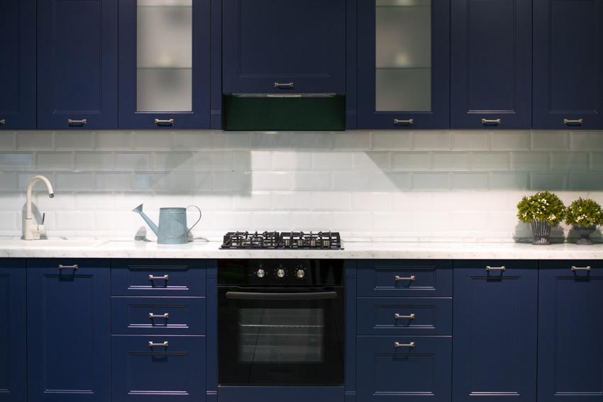 Blue kitchen cabinets white backsplash black oven