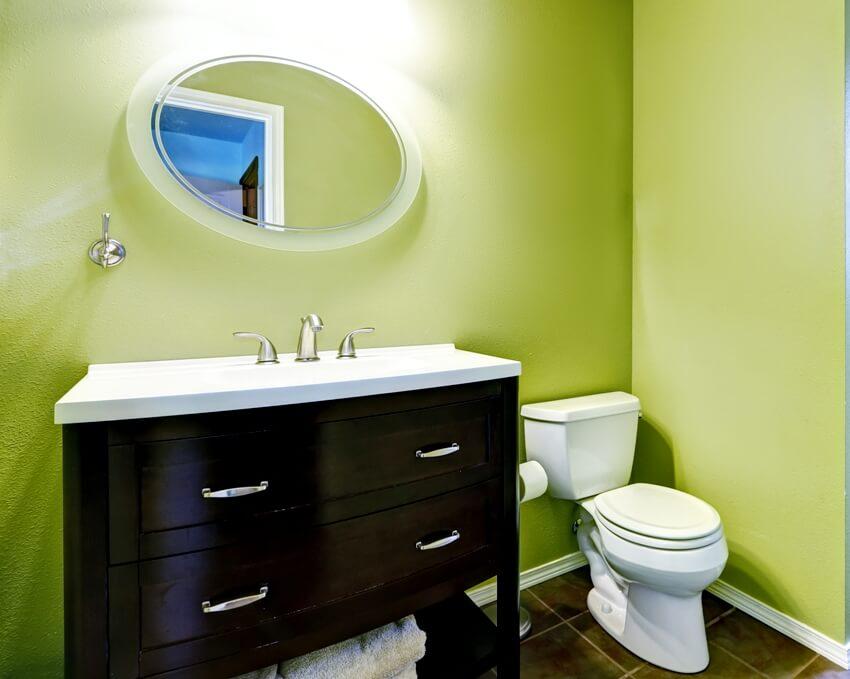 Bright green bathroom interior with brown bathroom vanity cabinet and mirror