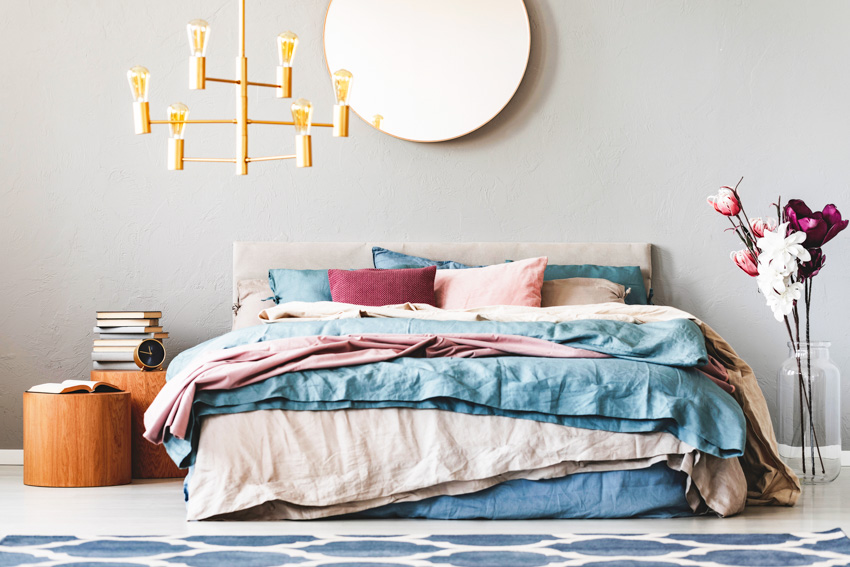 Circular mirror hanging above large bed with teal and pastel pink sheets and pillows