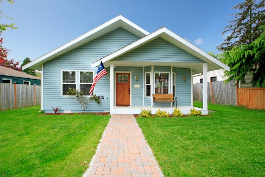Clapboard house brick walkway lawn wood front door