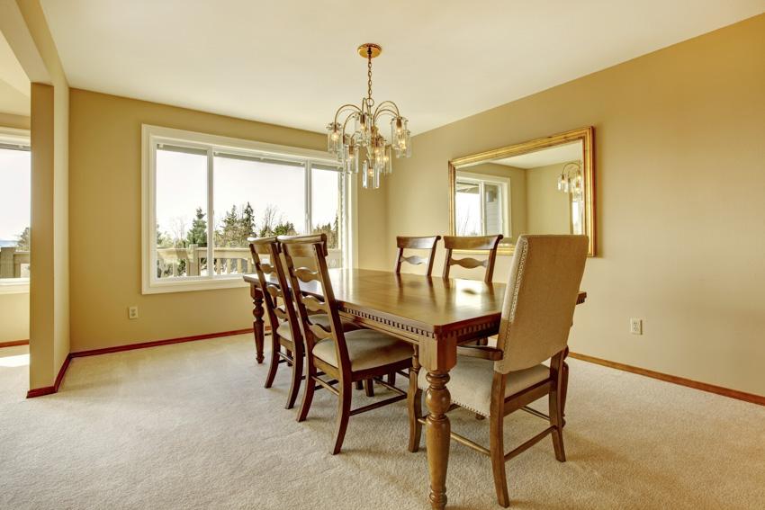 Classic wood table dining room carpet floor chandelier windows yellow walls