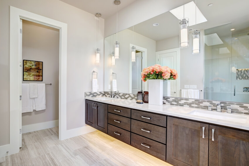Contemporary master bathroom features a dark dual vanity cabinet and white countertop with mosaic backsplash under a large full mirror