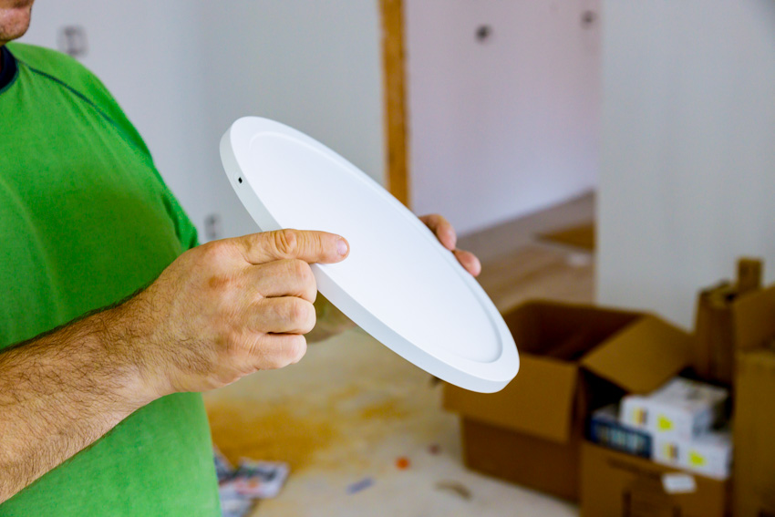 Contractor inspecting thin canless recessed light