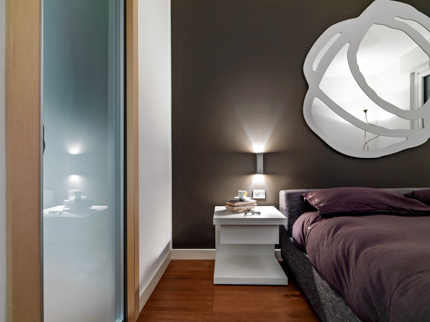 Custom mirror hanging above bed glass divider table lamp