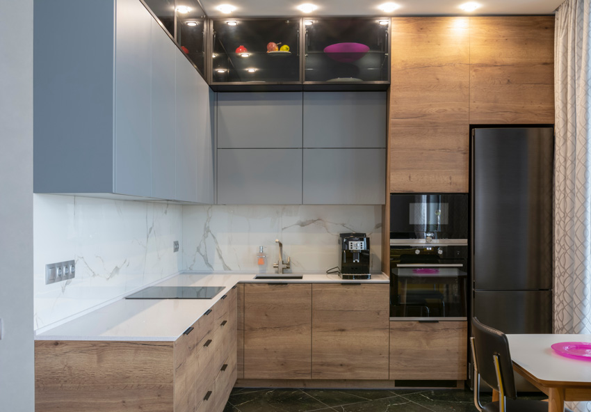 Gray and wood cabinets black oven and refrigerator white countertop