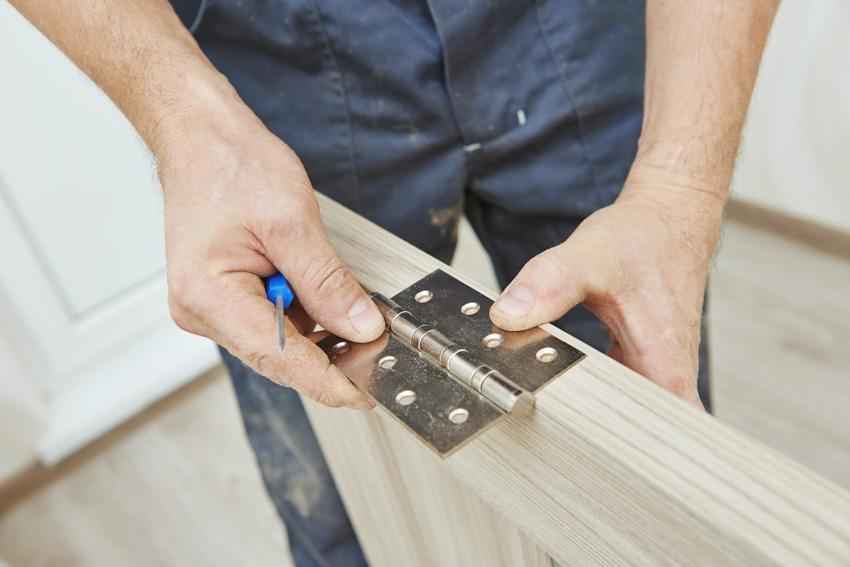 Handyman installing hinge on jib door