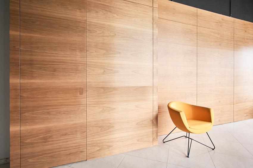 Hidden door wood panel wall orange chair