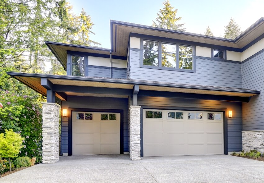Home exterior with contemporary house stone columns and two garage spaces