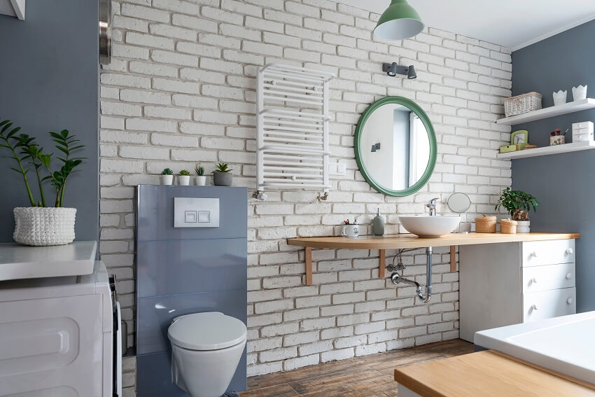 Interior of industrial bathroom in loft apartment with brick wall, grey decor, round mirror and wooden furniture