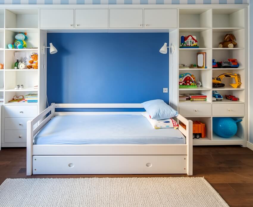 Kid's room in a modern style with a white bed with side rails and pillows lockers and shelves with toys