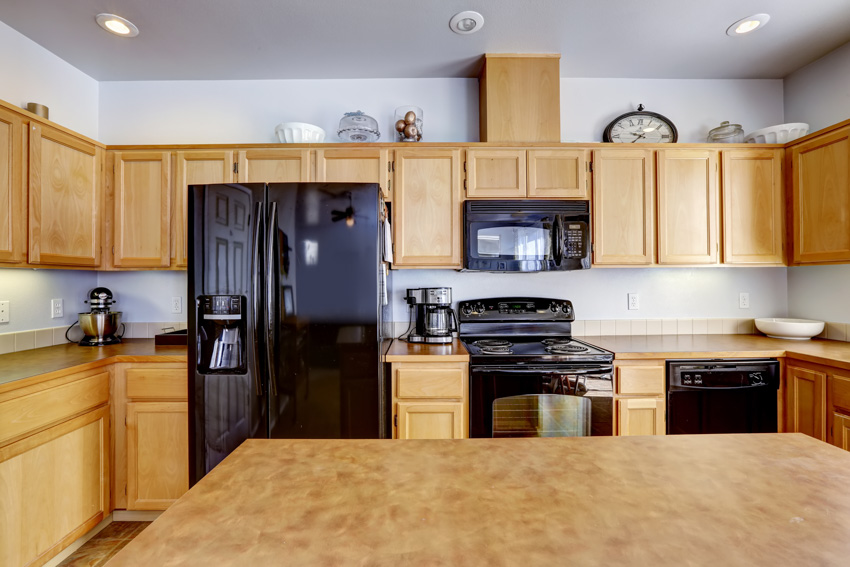 Light brown kitchen with black stainless steel appliances